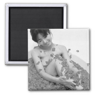 Woman relaxing in hot tub with flower petals, magnet