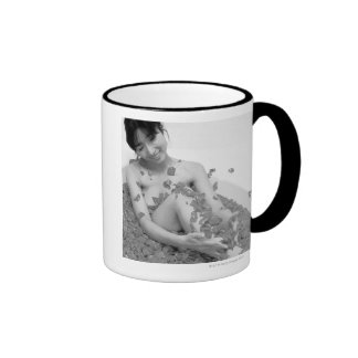 Woman relaxing in hot tub with flower petals, coffee mugs