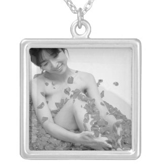 Woman relaxing in hot tub with flower petals, pendant