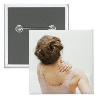 Woman rubbing aching back pinback button