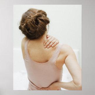 Woman rubbing aching back poster