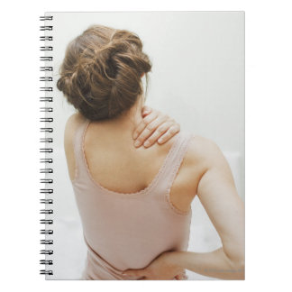 Woman rubbing aching back spiral notebook