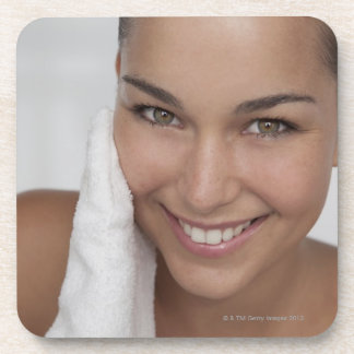 Woman scrubbing her face with cloth beverage coasters