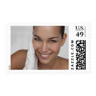 Woman scrubbing her face with cloth postage stamp