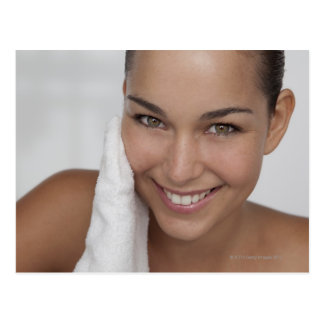 Woman scrubbing her face with cloth postcard