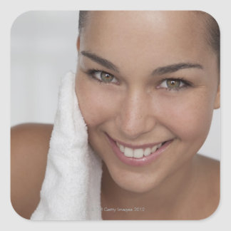 Woman scrubbing her face with cloth square sticker