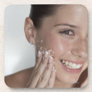 Woman scrubbing sugar on her face beverage coaster