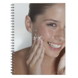 Woman scrubbing sugar on her face notebook