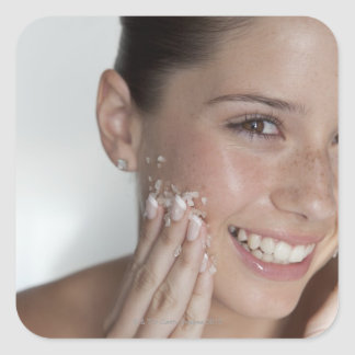Woman scrubbing sugar on her face sticker