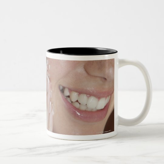 Woman scrubbing sugar on her face Two-Tone coffee mug