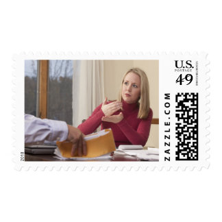 Woman signing the word 'Mortgage' in American Postage