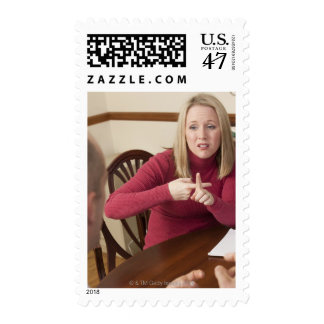 Woman signing the word 'Rent' in American Sign Postage