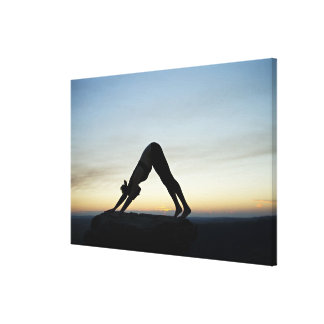 woman silhouetted against the sunset practicing canvas print