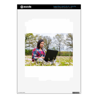 Woman sits with laptop in blooming meadow decal for iPad 3