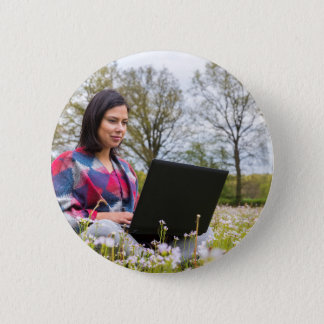 Woman sits with laptop in blooming meadow pinback button