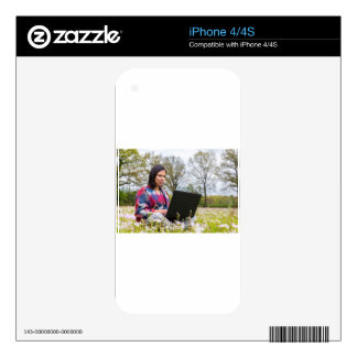 Woman sits with laptop in blooming meadow skin for iPhone 4S
