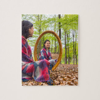 Woman sits with mirror in forest during spring jigsaw puzzle