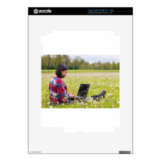 Woman sitting with laptop in spring meadow iPad 2 skin