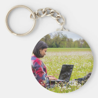 Woman sitting with laptop in spring meadow keychain