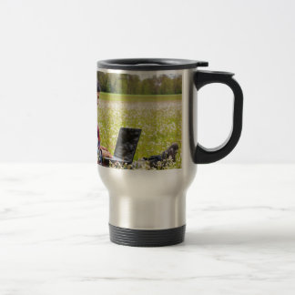 Woman sitting with laptop in spring meadow travel mug