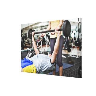 Woman spotting man lifting barbell canvas print