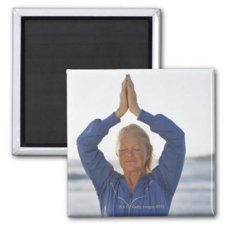 Woman standing with hands clasped overhead magnet