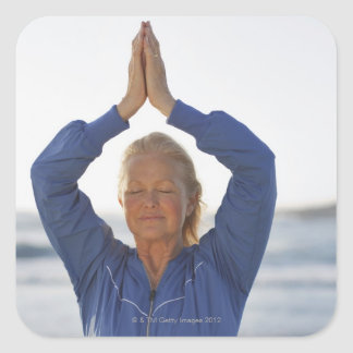 Woman standing with hands clasped overhead square sticker