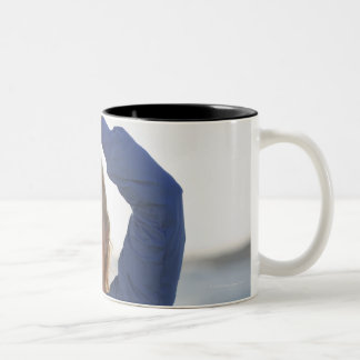 Woman standing with hands clasped overhead Two-Tone coffee mug