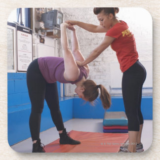 Woman stretching with trainer in gym coaster