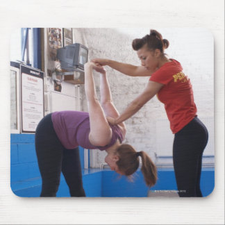 Woman stretching with trainer in gym mouse pad