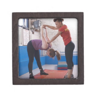 Woman stretching with trainer in gym premium jewelry box