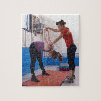 Woman stretching with trainer in gym puzzle