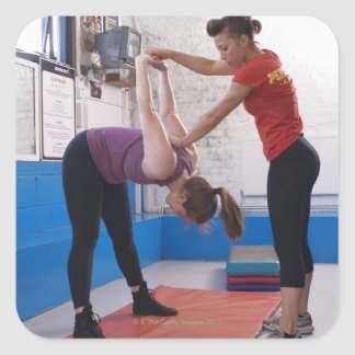 Woman stretching with trainer in gym square sticker