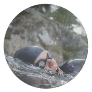 Woman swimming, close-up dinner plate