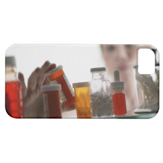 Woman taking pills from medicine cabinet iPhone 5 cases