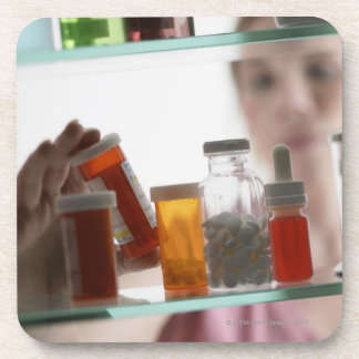 Woman taking pills from medicine cabinet drink coaster