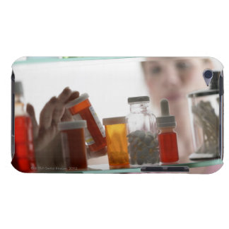 Woman taking pills from medicine cabinet iPod touch case