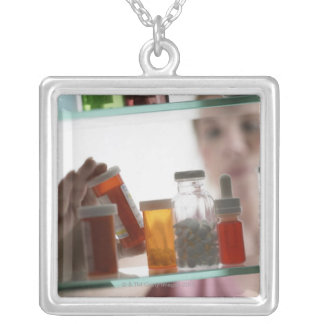 Woman taking pills from medicine cabinet pendants