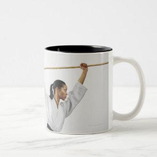 Woman using bow staff Two-Tone coffee mug