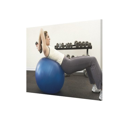 Woman using exercise ball and hand weights canvas print