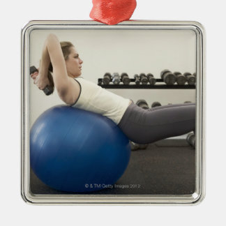 Woman using exercise ball and hand weights metal ornament