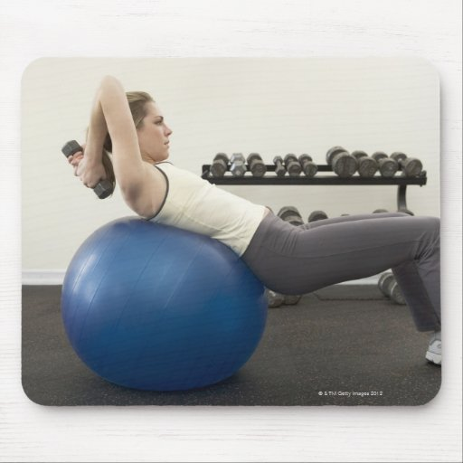 Woman using exercise ball and hand weights mousepad