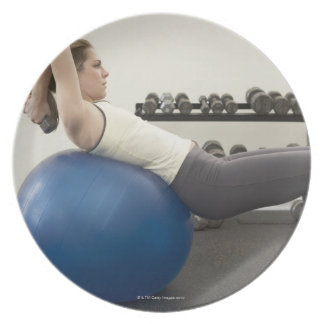 Woman using exercise ball and hand weights party plates