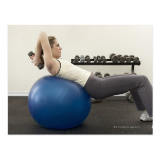 Woman using exercise ball and hand weights postcard