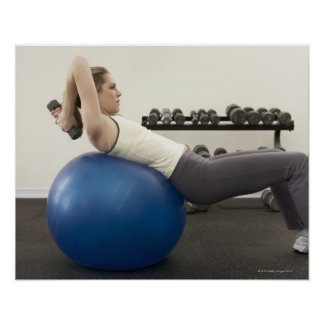 Woman using exercise ball and hand weights poster