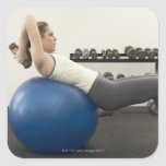 Woman using exercise ball and hand weights square sticker