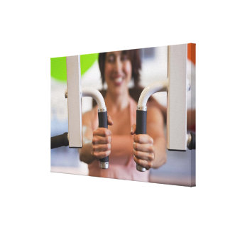 Woman using exercise machine in gym gallery wrap canvas