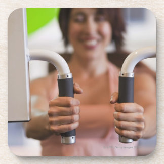 Woman using exercise machine in gym drink coaster