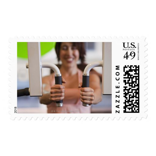 Woman using exercise machine in gym stamps