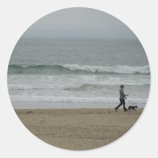 Woman Walking Dog Along Pismo Beach, CA Classic Round Sticker